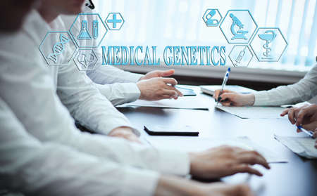 A group of doctors in a modern clinic is planned. The concept of modern medicine and medical biotenology. Medical icons on the screen with the inscription: MEDICAL GENETICS