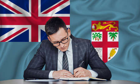 A businessman in a jacket and glasses sits at a table signs a contract against the background of a flag Fiji