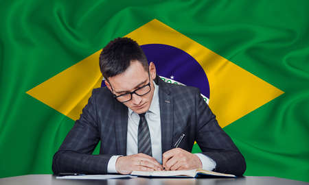 A businessman in a jacket and glasses sits at a table signs a contract against the background of a flag Brazil