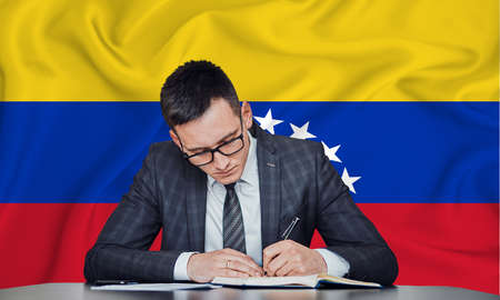 A businessman in a jacket and glasses sits at a table signs a contract against the background of a flag Venezuela