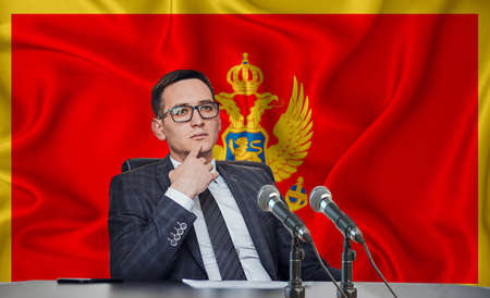 Young man in glasses and a jacket at an international meeting or press conference negotiations, on the background of the flag Montenegro
