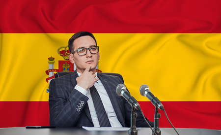 Young man in glasses and a jacket at an international meeting or press conference negotiations, on the background of the flag Spain Stock Photo