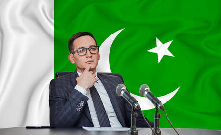 Young man in glasses and a jacket at an international meeting or press conference negotiations, on the background of the flag Pakistan