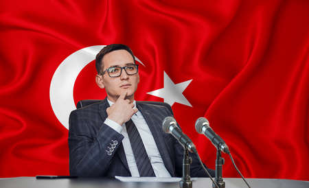 Young man in glasses and a jacket at an international meeting or press conference negotiations, on the background of the flag Turkey