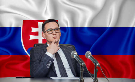 Young man in glasses and a jacket at an international meeting or press conference negotiations, on the background of the flag Slovakia