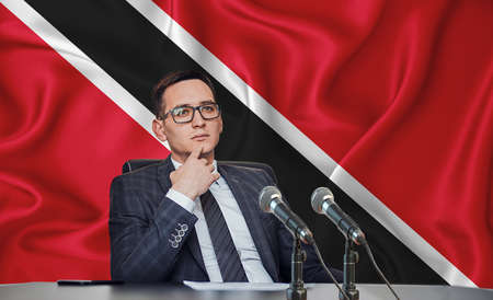 Young man in glasses and a jacket at an international meeting or press conference negotiations, on the background of the flag Trinidad and Tobago Stock Photo