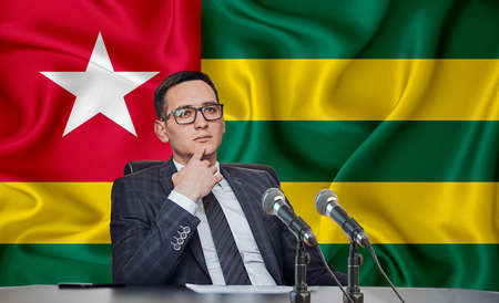 Young man in glasses and a jacket at an international meeting or press conference negotiations, on the background of the flag togo