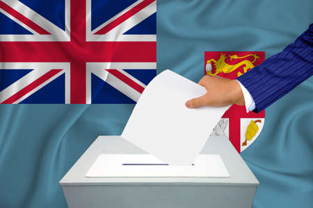 Elections in the country - voting at the ballot box. A man's hand puts his vote into the ballot box. Flag Fiji on background.