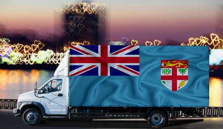 Fiji flag on the side of a white van against the backdrop of a blurred city and river. Logistics concept