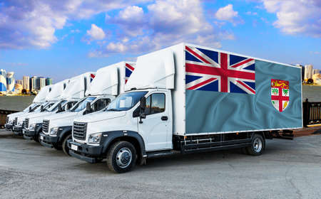 Fiji flag on the back of Five new white trucks against the backdrop of the river and the city. Truck, transport, freight transport. Freight and Logistics Concept