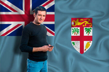 Fiji flag on the background of the texture. The young man smiles and holds a smartphone in his hand. The concept of design solutions. Stock fotó