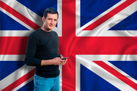 Great Britain flag on the background of the texture. The young man smiles and holds a smartphone in his hand. The concept of design solutions. Zdjęcie Seryjne