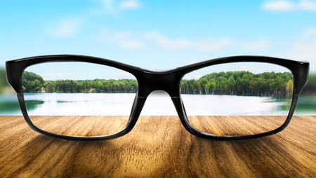 astigmatism: Clear lake in glasses on the background of blurred nature