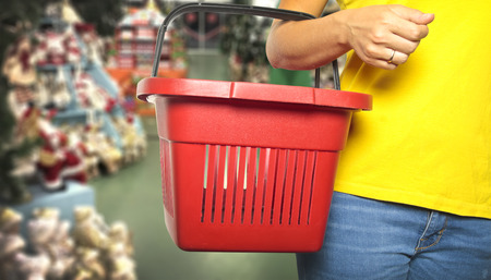 Woman holds a shopping basket on store background