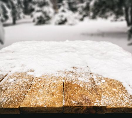 Wooden desk covered by snow and snowy park on background Banque d'images