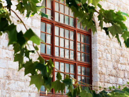 Old stone-faced building with wooden window frames in Haifa Israel Foto de archivo