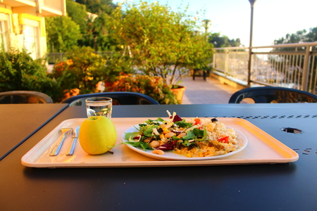 sallad: Traditional Italian dinner at a seaside and at a sunset with rice, salad, fish and an apple