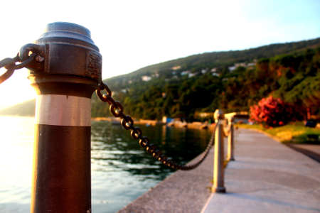 mediterranea: Seafront promenade at the Mediterranean sea before sunset with a chained fence