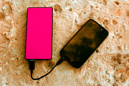 Magenta pink powerbank and smartphone on concrete background, top view