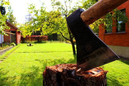 cleave: Axe on a stump in a garden with a lawn mower and a red house wall at the background Stock Photo
