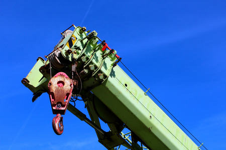Closeup of a green and red elevating crane against blue skye background Stock Photo