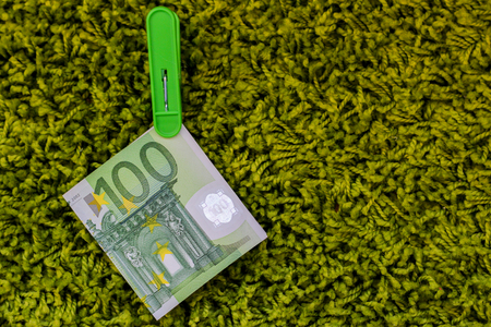 Green banknote 100 euro in a green clothes peg at a green background