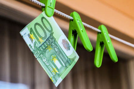 Green banknote 100 euro in a green clothes peg