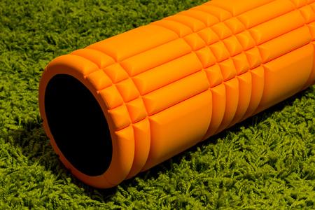 Orange foam roller on green carpet background