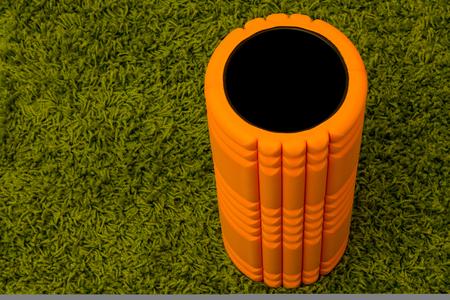 myofascial: Orange foam roller on green carpet background
