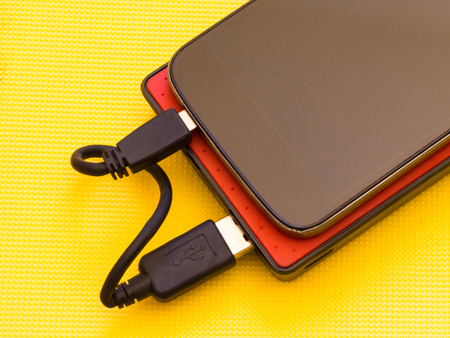 Black smart phone and red power bank on yellow background