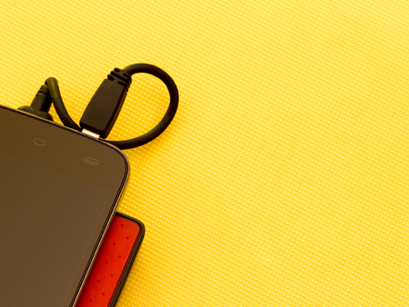 Black smart phone and red power bank on yellow background with copy space