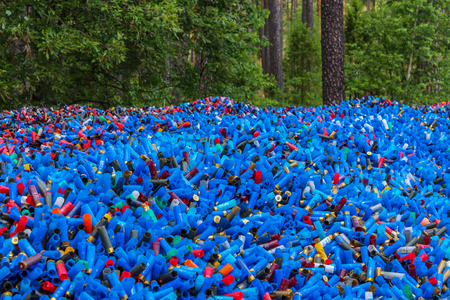 Pile of many empty colorful shotgun shells in a forest, mostly blue colored, with some red, white, yellow, green, cyane, and black, making motley pattern