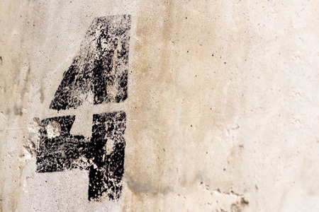 Black number four 4 painted on old light grey rugged concrete wall Imagens
