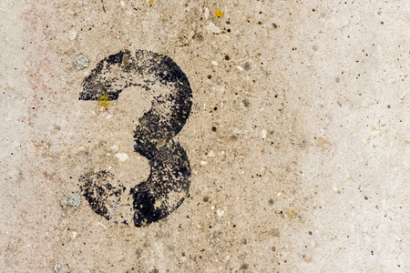 Black number three 3 painted on old rugged light grey concrete wall background with copy space