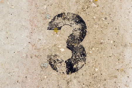 Black number three 3 painted on old rugged light grey concrete wall background