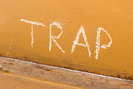 Word trap handwriting with white chalk on old orange metal background with a fly trapped in spider web in the corner Stock Photo