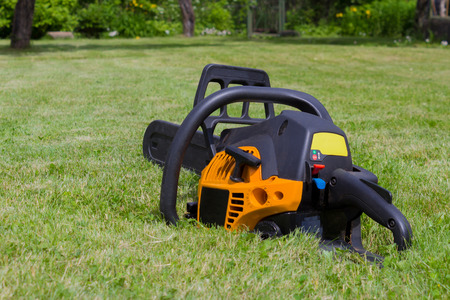 Black and orange chain saw on green grass meadow in a garden
