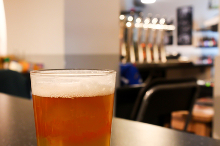 Full glass of light orange juicy tasty beer in a cozy light craft beer bar with shiny silver beer taps and grey wall background
