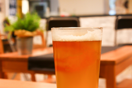 Full glass of light orange juicy tasty beer in a cozy light craft beer bar on a wooden table Banco de Imagens