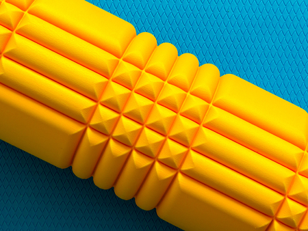 Yellow fitness foam roller on blue scale texture background top view