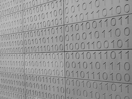 Zeroes and ones digital binary pattern on grey wall background Stock Photo
