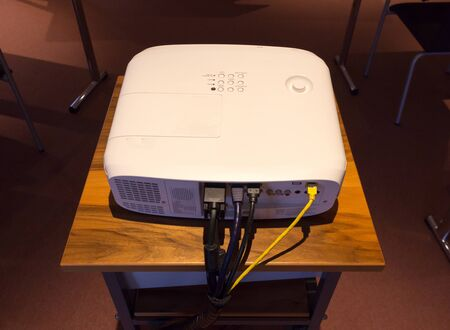 White screen projector  on a wooden stance in a dark conference or lecture hall