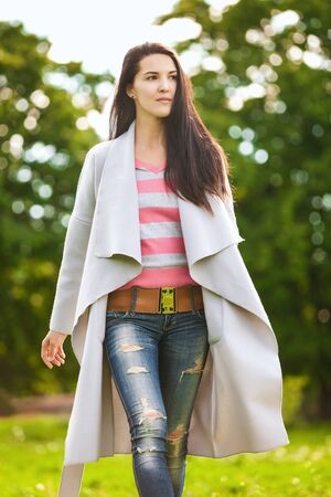 confidently: girl confidently goes on a lawn on a spring morning