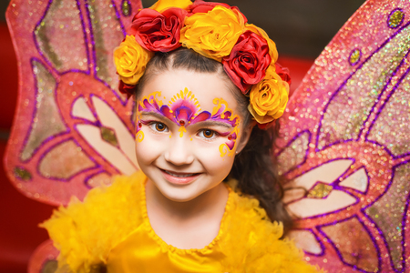 fairy wings: child with fairy wings in yellow shirt and body art