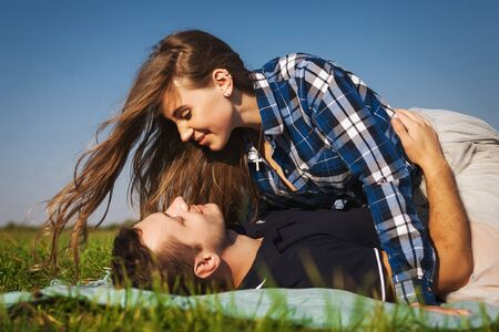 teenagers lie on the grass. girl  top of the guy Stock Photo - 70021520