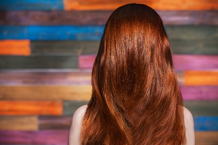 strips away: young beautiful red-haired girl standing back to the camera