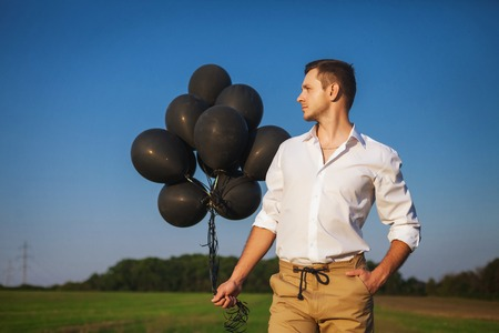 purposefulness: man with black balloons standing in field and looks into the distance Stock Photo