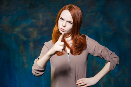 Strict red haired girl shows finger with arms akimbo Stock Photo