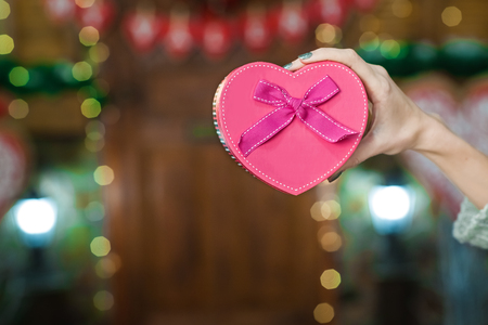 woman hand holding pink box in the form of heart Stock Photo