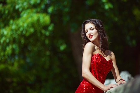 Sexy woman with dark curly long hair in red dress